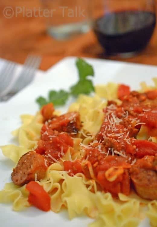 A close up of a plate of pasta with sausage.