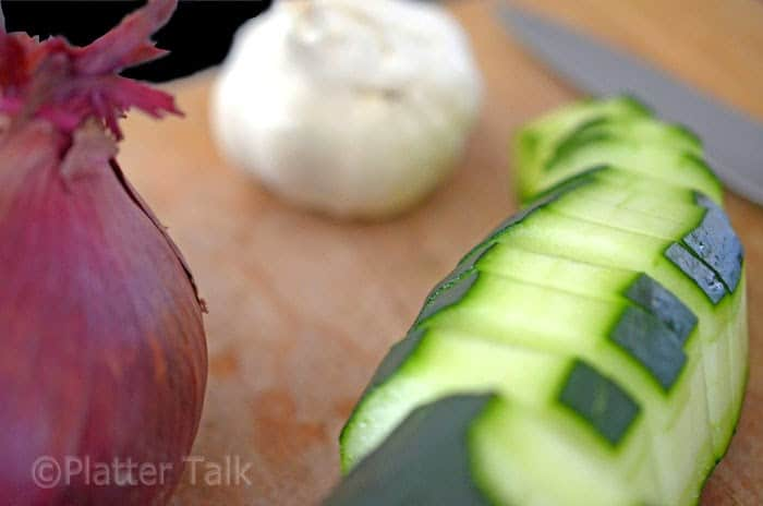 A close up of a garlic, red onion and sliced cuke on cutting board with knife