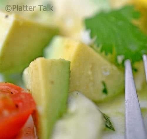 Close up diced avocado, cuke, tomato and cilantro