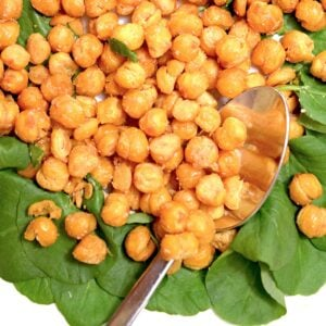 A dish of baked chickpeas on a bed of lettuce.