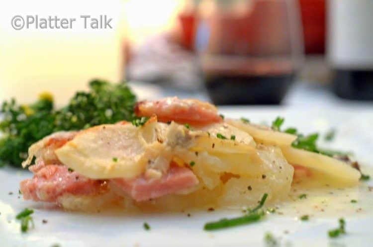A close up of a plate of scalloped potatoes and ham