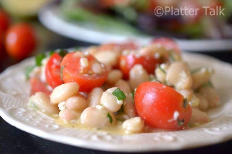 A close-up of tomato salad with white beans.