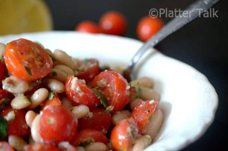 A bowl of tomato salad with white beans.