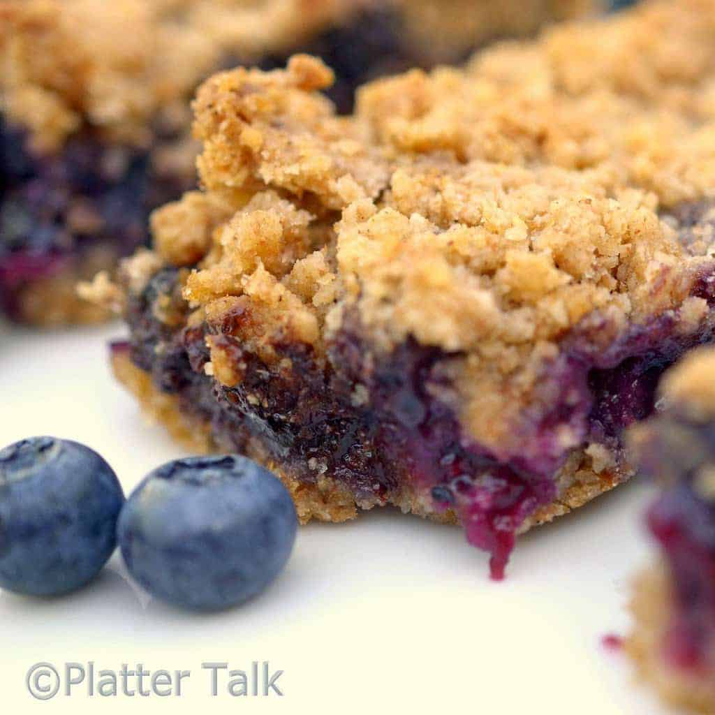 A close up of a blueberry bar on a plate.