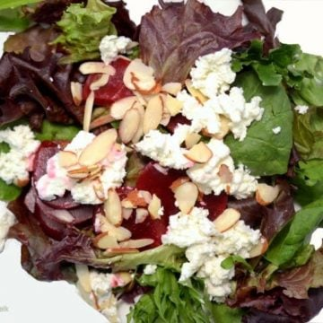 A plate of salad with beets and goat cheese.