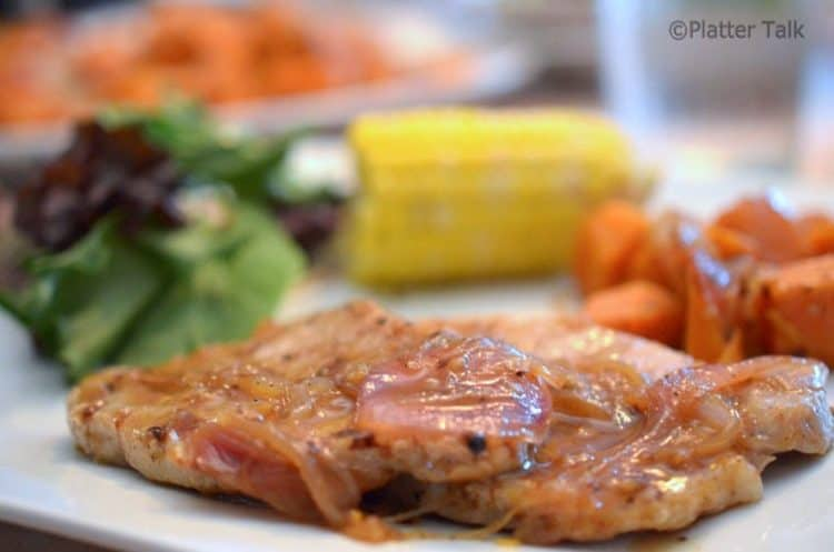 A pork chop on a plate.