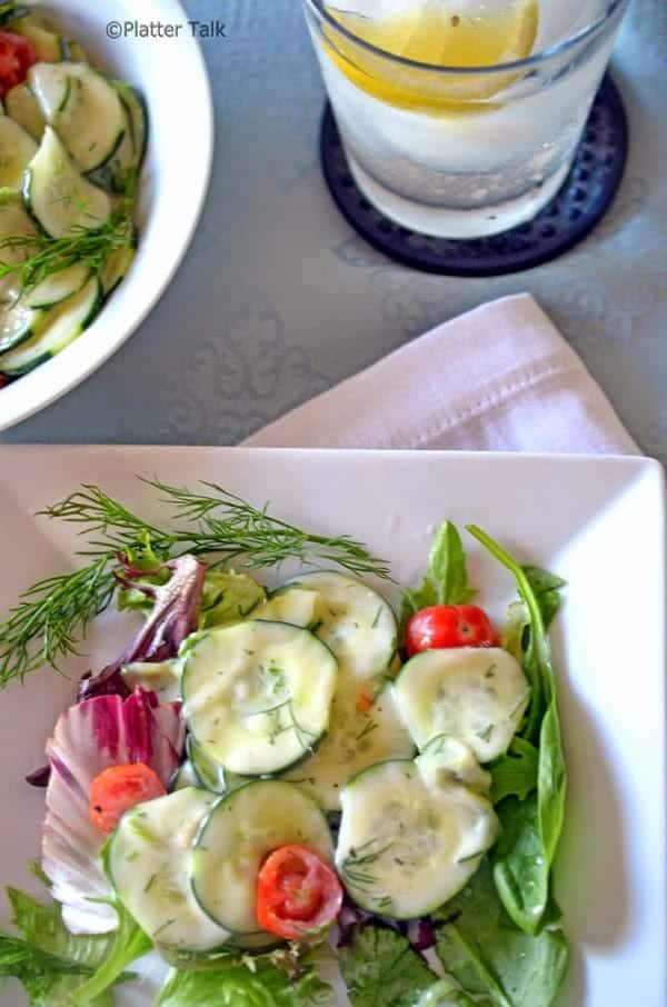 A plate of salad with cucumbers.