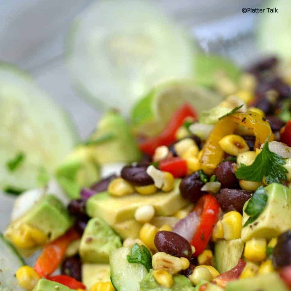 Corn salsa in a bowl with cucumber chips.
