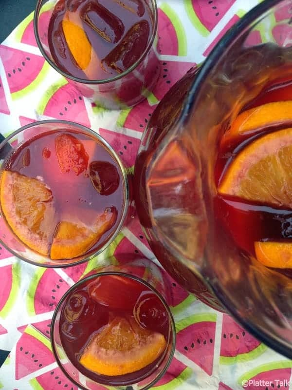 Pitcher of red wine sangria with orange slices and ghree glasses.