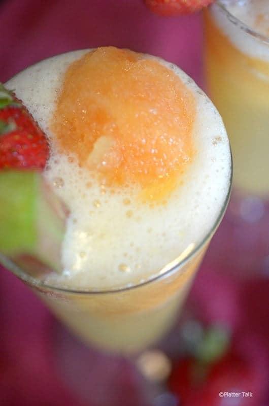 A close up of a glass of rhubarb slush garnished with fruit