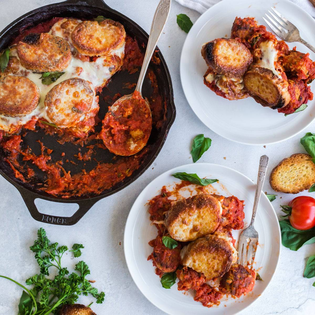 A skillet and two plates of meatball sub casserole