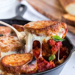 Scooping a portion of meatballs and bread out of skillet with melted cheese.