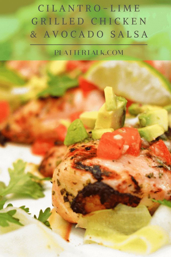 Grilled chicken on a serving platter garnished with lime and avocado salsa.