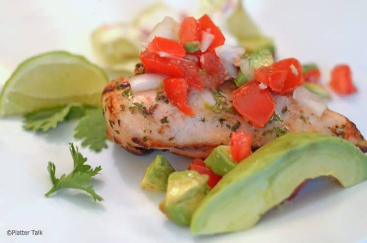 Portion of grilled chicken with avocado an lime garnish.