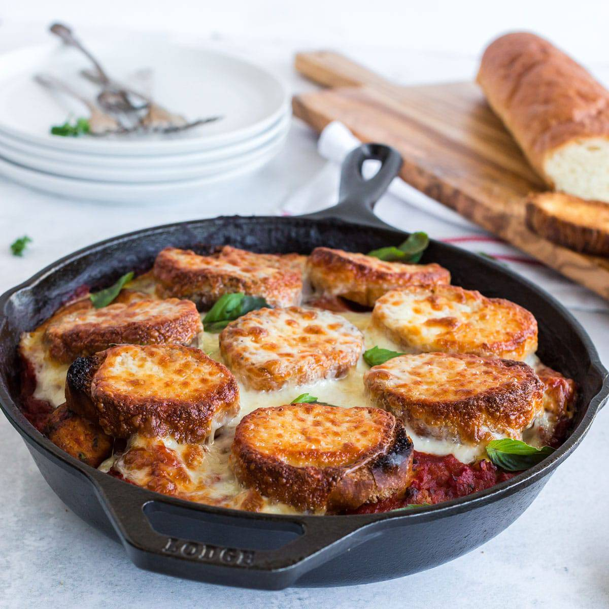 Skillet with sliced baguettes and melted cheese in red sauce.