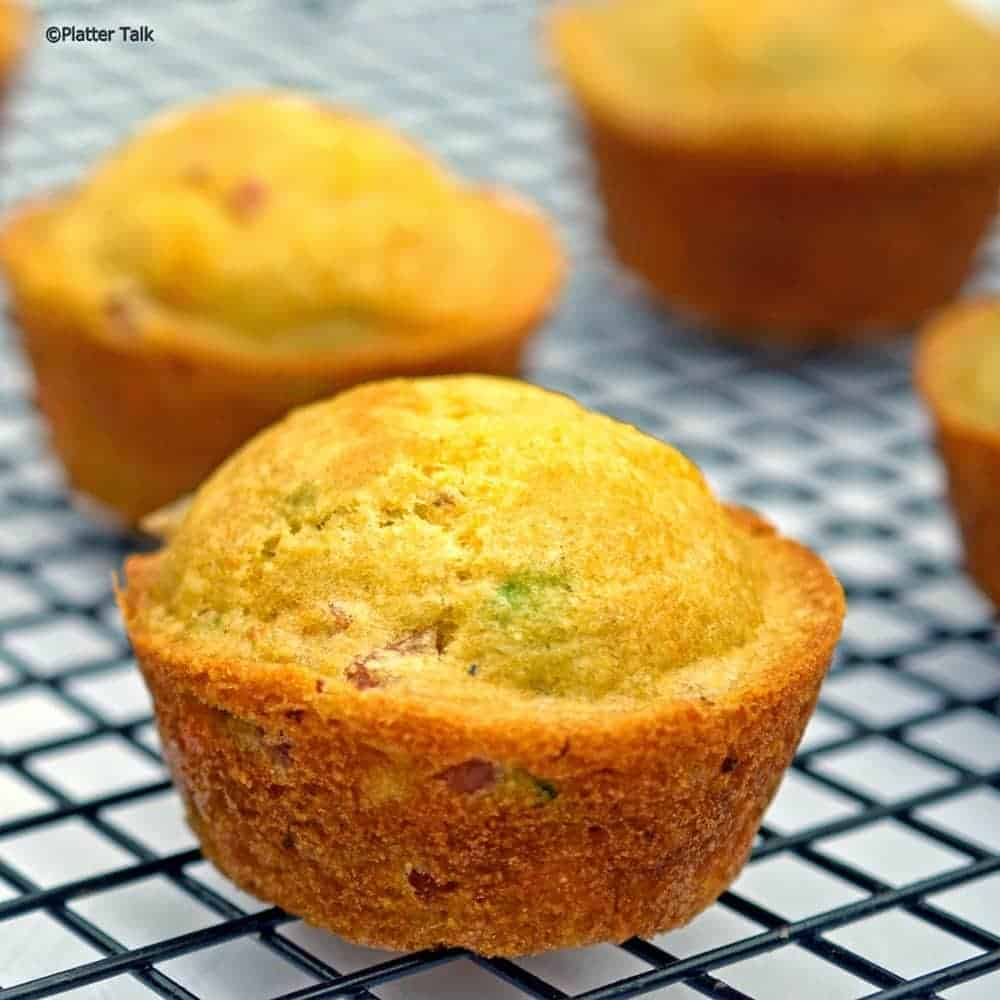 Ham and cheese cornmeal muffins on a cooling rack.