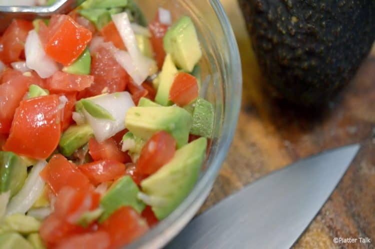 Bowl of ingredients for avocado salsa.