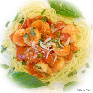 a plate of garlic basil shrimp with pasta.