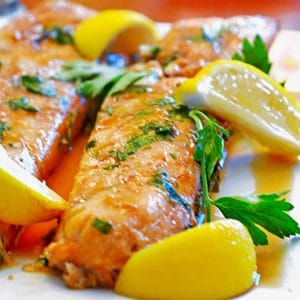 Haddock on plate with lemon and parsley.