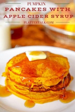 Pumpkin Pancakes stacked on a plate with a pad of butter and dripping syrup.