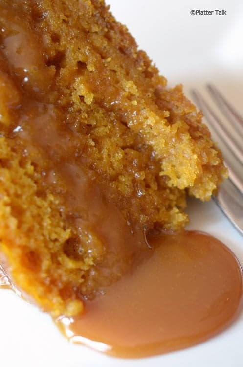 Wedge of slow cooker pumpkin cake dessert with caramels sauce oozing off it.