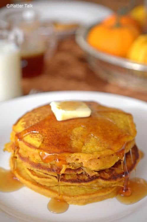 Stack of Pumpkin Pancakes on a white plate with butter and dripping syrup.