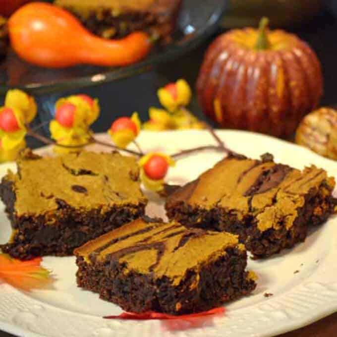 A plate of brownies with a pumpkin in the background.