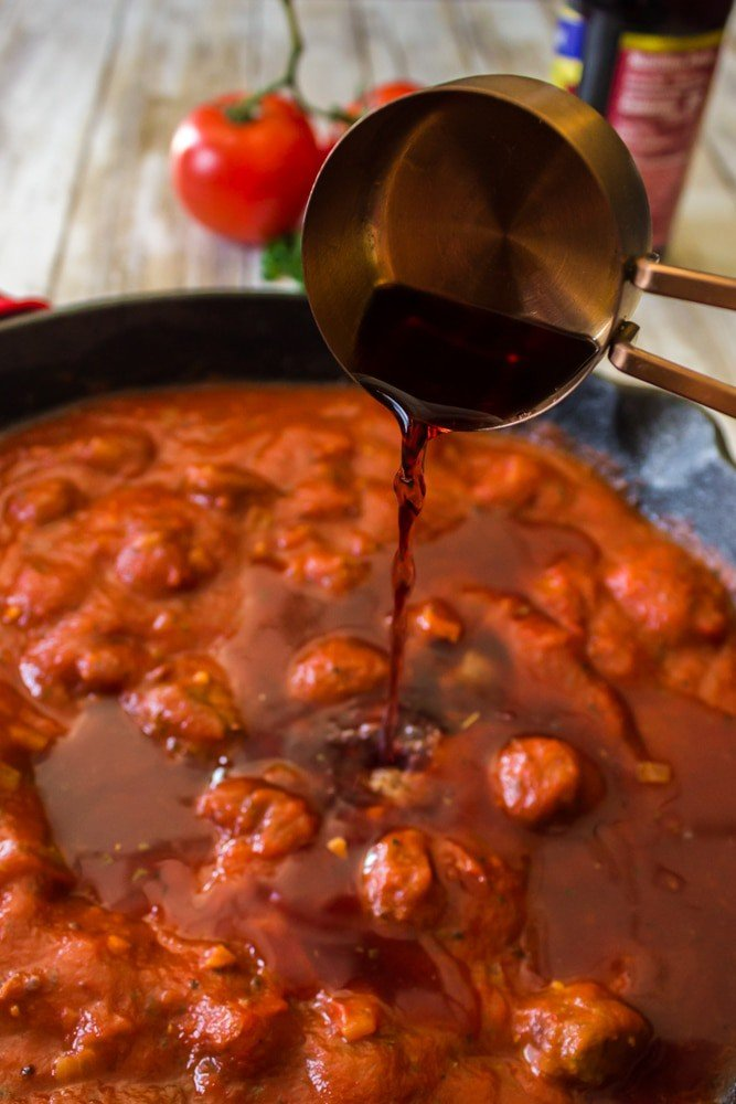 Red wine being added to lasagana sauce.