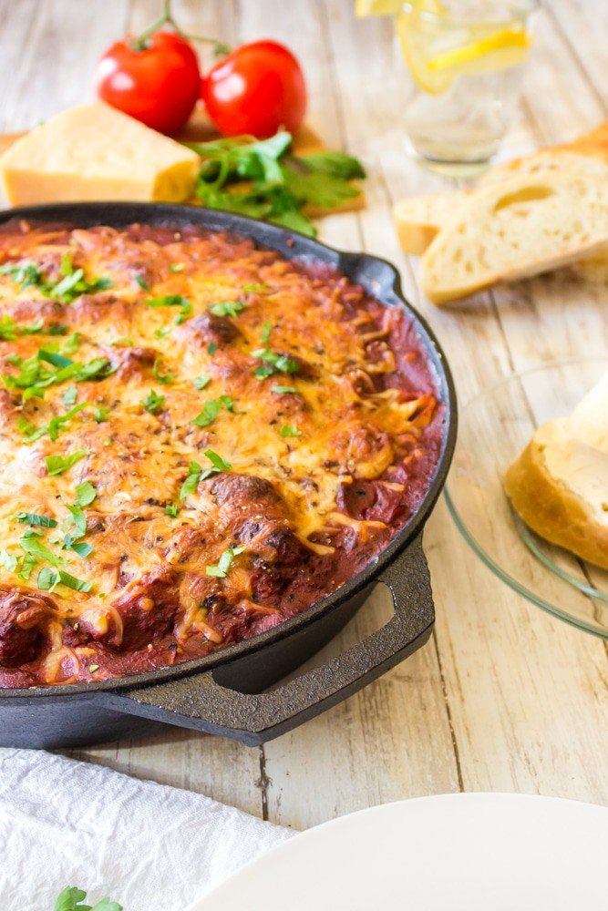 Skillet of lasagna with cheese and bread.
