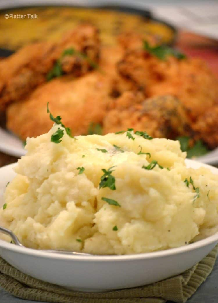 bowl of mashed potatoes with fried chicken.