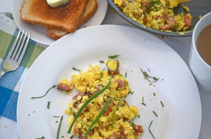 a plate of scrambled eggs and ham.