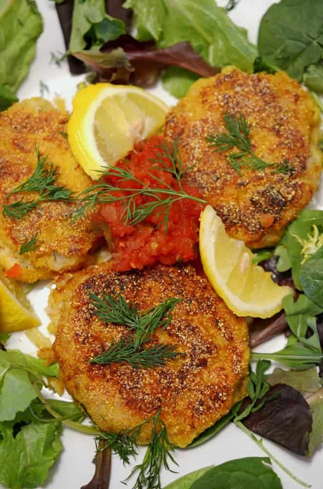 A plate of fish cakes with lemon and dill.