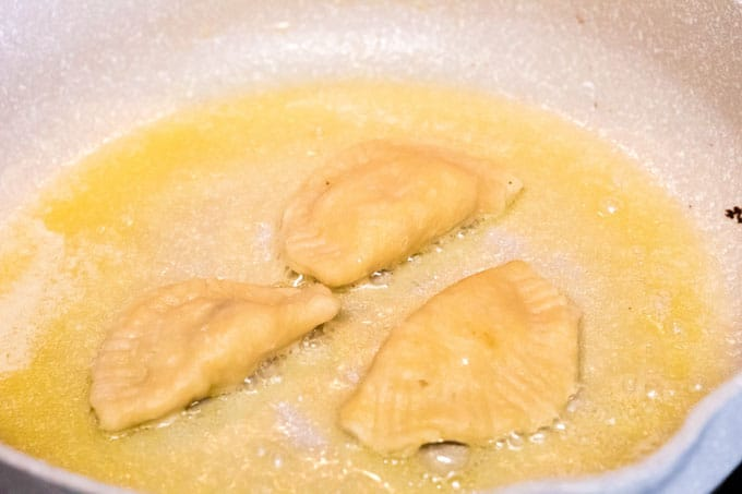 Browning pierogi in a frying pan.