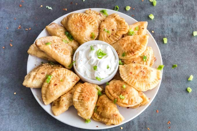 Plate of Pierogi with sour cream in center.