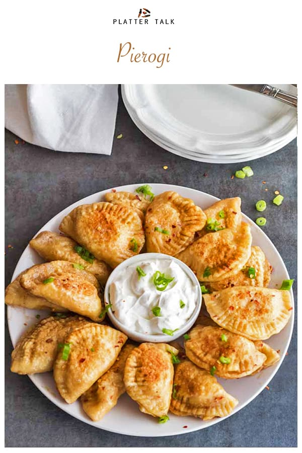 Plate of pierogi with sour cream and chives.