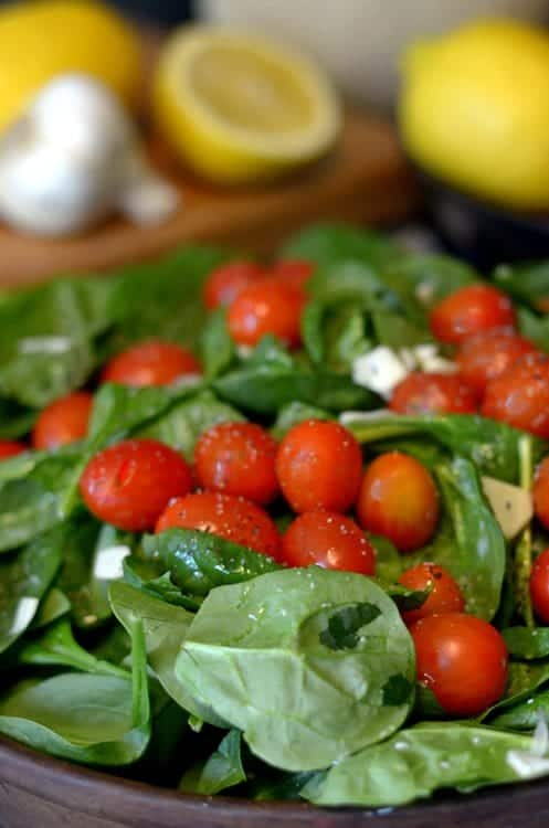 A plate is filled with fresh fruit and vegetables, with Spinach on a platter.