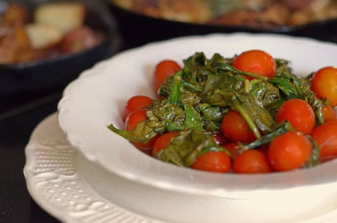 A plate of food on a table with spinach and tomato.