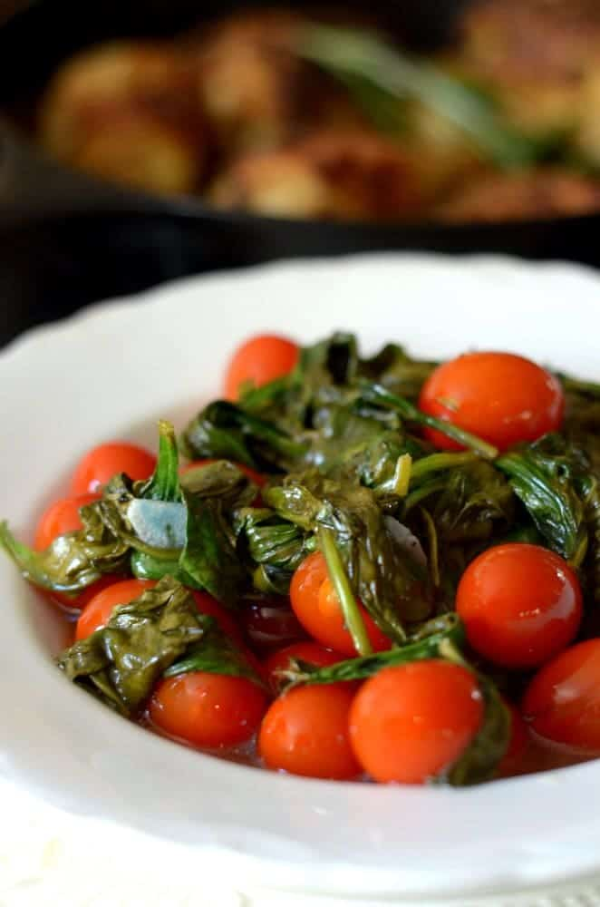 White bowl of cherry tomatoes mixed with roasted spinach.