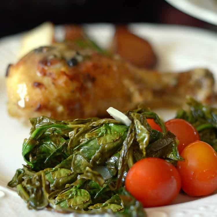 Chicken drumstick on a dinner plate with wilted spinach and cherry tomatoes.