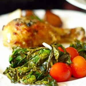 Roasted spinach with a chicken drumstick on a plate.