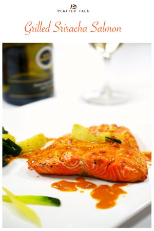 A serving of salmon on a white plate and a glass of white wine