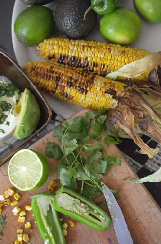 Grilled sweet corn on the cob, with avocado, lime, and jalapeno pepper on a cutting board.