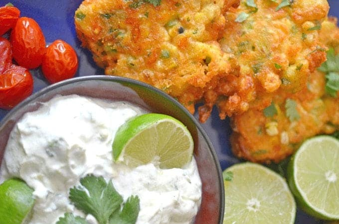 Plate of corn fritters on a blue plate with roasted cherry tomatoes and a creamy sauce with limes.