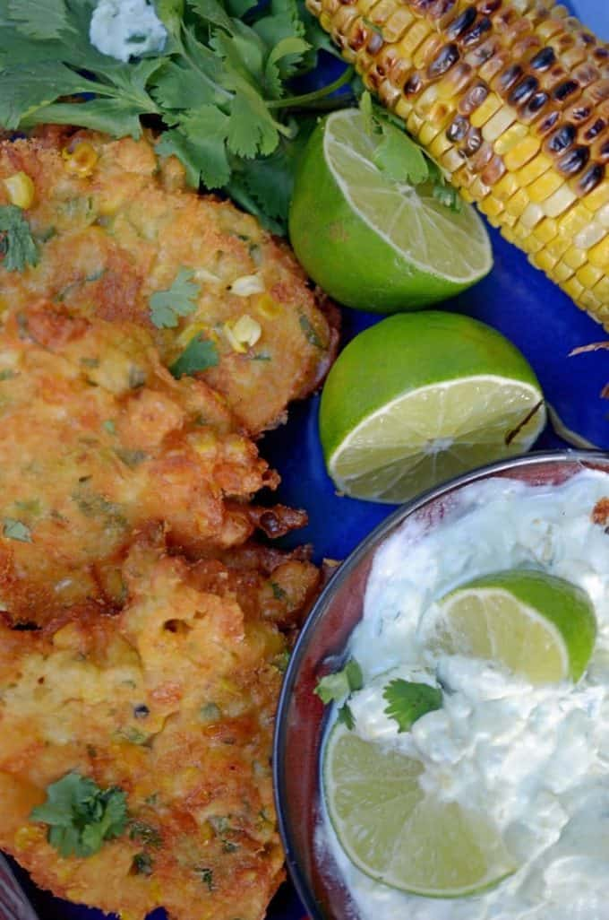 Plate of fresh corn fritters with lime wedges and grilled corn on the cob.