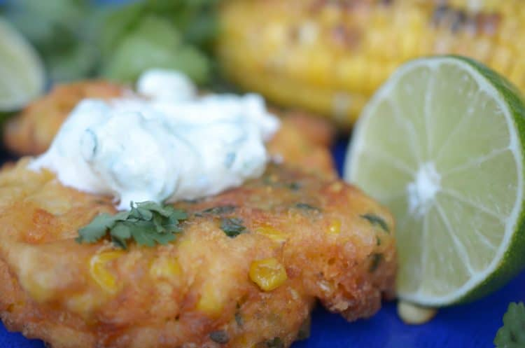 Corn fritter, topped with cream sauce and a half of lime.