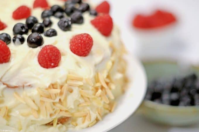 White layer cake with raspberries and almond slivers.