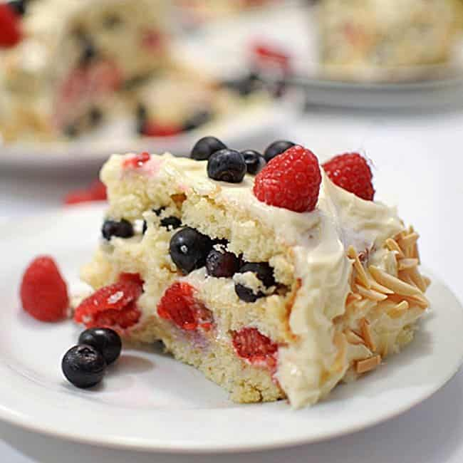 Slice or white cake with raspberries and blueberries.