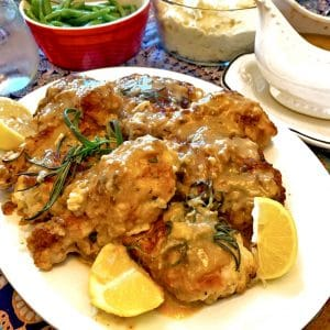 Plate of chicken with lemon and fresh rosemary.
