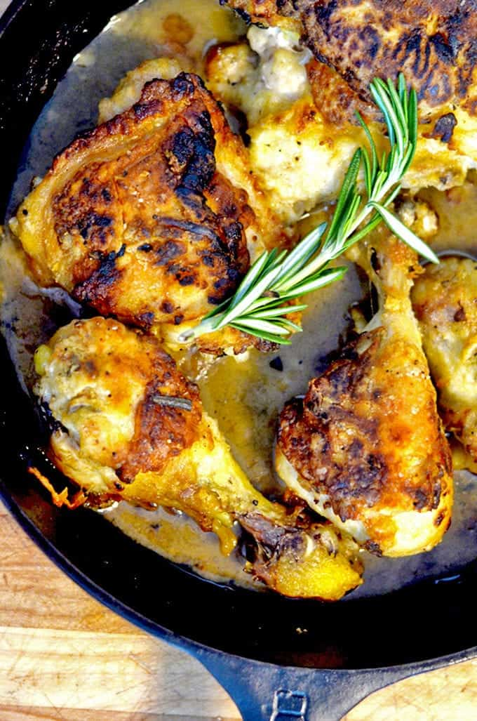 Browned chicken in a skillet with fresh rosemary garnish.