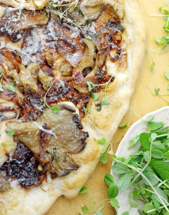 A close-up of food, with Pizza and Shallots and musrhooms.